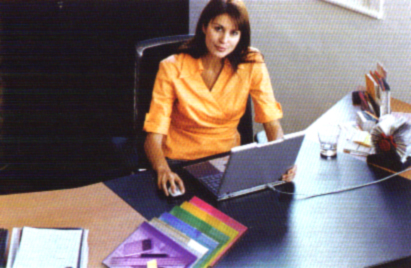 Woman using Tarifold poly envelopes to great advantage at her desk.